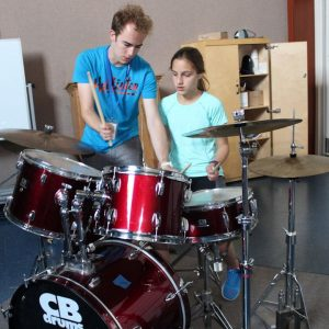 Camper getting creative playing drums at Amerian summer camp
